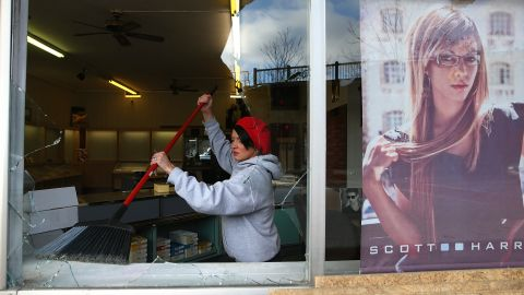 A woman cleans up glass from a business' shattered window on November 25.
