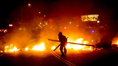 A protester adds wood to a fire burning in Oakland, California, on November 25.