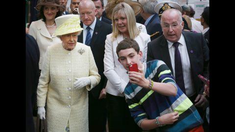 A boy in Belfast, Northern Ireland, takes a selfie in front of Britain's Queen Elizabeth II on Tuesday, June 24.