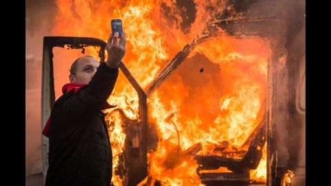 A protester takes a selfie in front of a burning car in Brussels, Belgium, on Thursday, November 6. Tens of thousands of demonstrators converged on the Belgian capital to protest government policies that would extend the pension age, contain wages and cut into public services.