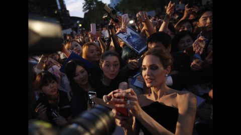 """Actress Angelina Jolie tries to take pictures with fans as she attends the Tokyo premiere of her movie """"Maleficent"""" on Monday, June 23. <a href=""""http://www.cnn.com/2013/05/14/showbiz/gallery/angelina-jolie/index.html"""" target=""""_blank"""">See the life of Angelina Jolie</a>"""