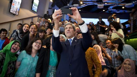 """U.S. Secretary of State John Kerry takes a selfie with a group of students in Jakarta, Indonesia, before delivering <a href=""""http://www.cnn.com/2014/02/16/politics/kerry-climate/index.html"""">a speech on climate change</a> on Sunday, February 16."""