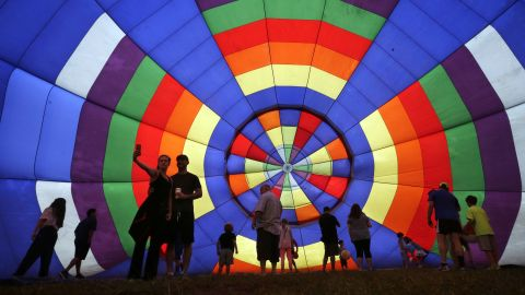 People walk around a partially inflated hot-air balloon Sunday, July 27, at the New Jersey Festival of Ballooning in Readington, New Jersey.