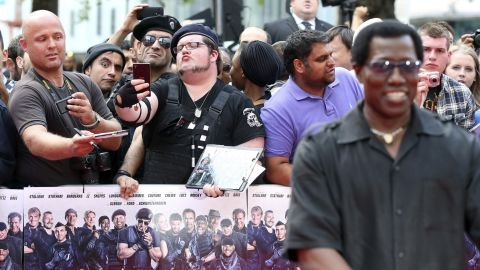 """Fans take selfies Monday, August 4, as actor Wesley Snipes, right, arrives for the world premiere of """"The Expendables 3"""" in London."""