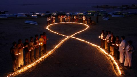 Indian villagers hold oil lamps as they surround a huge AIDS symbol on the beach at Nalsarovar on November 30, 2009, the eve of World Aids Day.