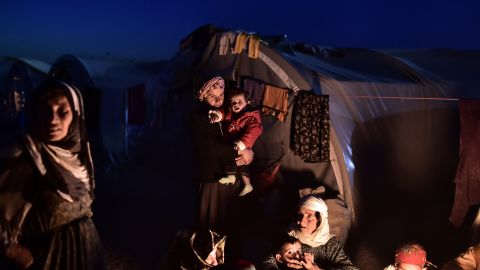 Syrian Kurdish refugees sit outside tents at a camp in Suruc on November 11.