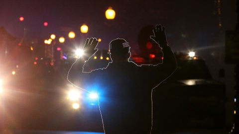"""A protester in Ferguson, Missouri, stands in front of police vehicles with his hands up on November 24, 2014. A grand jury's decision not to indict police Officer Darren Wilson in the killing of Michael Brown prompted<a href=""""http://www.cnn.com/2014/11/24/justice/gallery/ferguson-reaction/index.html""""> waves of protests in Ferguson</a> and across the country. The """"hands up, don't shoot"""" gesture became a rallying cry and protest symbol."""