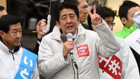 """Surrounded by candidates of the ruling Liberal Democratic Party, Japanese Prime Minister Shinzo Abe (C) gestures as he delivers a speed during hisstumping tour for the December 14 general election in Sendai, Miyagi prefecture, on December 2, 2014. Official campaigning kicked off for a snap national poll in two weeks, with Prime Minister Abe describing it as a referendum on his faltering """"Abenomics"""" economic growth blitz. AFP PHOTO/Toru YAMANAKATORU YAMANAKA/AFP/Getty Images"""