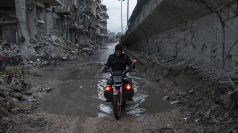 A man drives his motorcycle through a puddle in Aleppo on Wednesday, November 26.