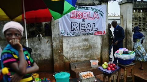 """""""When someone you love is sick, you want to hold that person, you want to carry them,"""" said Johansen. """"But you can't."""" In Freetown, a sign warning of the dangers of Ebola hangs outside a government hospital."""