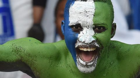"""Football is """"like a second religion in Sierra Leone."""" That was before the Ebola outbreak put a stop to organized games, casual kick-abouts, and people gathering to watch the national sport. Here, a fan shows his colors."""
