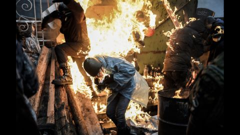 """Protesters in Kiev, Ukraine, catch fire as they stand behind burning barricades during clashes with police on February 20, 2014. Kiev's Independence Square had been the center of <a href=""""http://www.cnn.com/2014/02/19/world/gallery/ukraine-protests-0218/index.html"""">anti-government protests</a> since November 2013, when President Viktor Yanukovych reversed a decision on a trade deal with the European Union and instead turned toward Russia."""