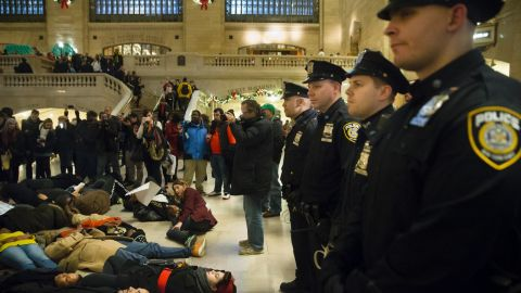 """Police stand guard as protesters participate in a """"die-in"""" December 6 at Grand Central Station in New York."""