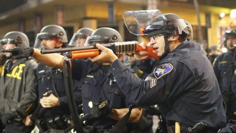 A police officer raises a shotgun toward the crowd in Berkeley on Saturday, December 6.