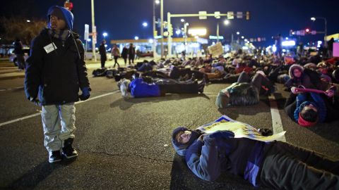 """Seven-year-old Elijah Owens, left, stands by people participating in a """"die-in"""" demonstration outside the Philadelphia Eagles' stadium in Philadelphia on Sunday, December 7."""