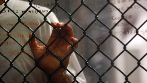 GUANTANAMO BAY, CUBA - OCTOBER 28: (EDITORS NOTE: Image has been reviewed by U.S. Military prior to transmission) A detainee stands at an interior fence at the U.S. military prison for 'enemy combatants' on October 28, 2009 in Guantanamo Bay, Cuba. Although U.S. President Barack Obama pledged in his first executive order last January to close the infamous prison within a year's time, the government has been struggling to try the accused terrorists and to transfer them out ahead of the deadline. Military officials at the prison point to improved living standards a
