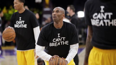 """Los Angeles Lakers' Kobe Bryant, center, warms up before an NBA basketball game against the Sacramento Kings on Tuesday, December 9, in Los Angeles. The team wore """"I Can't Breathe"""" shirts during warm-ups in support of the family of Eric Garner. Since a grand jury declined to indict a New York police officer in the death of Garner, demonstrators across the country have taken to the streets to express their outrage. Garner, a 43-year-old asthmatic, died in July after he was put in a chokehold by the officer, Daniel Pantaleo."""