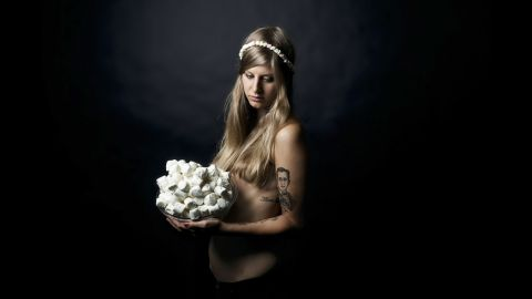 """A model poses with marshmallows. The models are friends of Ruetten's, usually with tattoos and piercings. """"It underlines the concept that they are 'children of the modern age,' having been brought up in the changing America, often defined by the culture of fast food,"""" Ruetten said."""