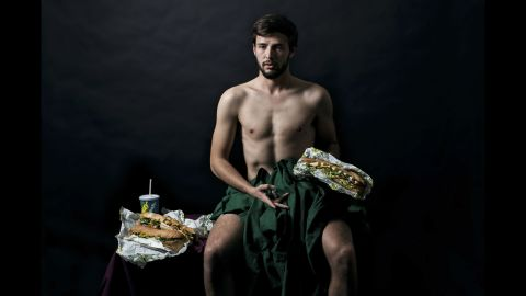 A man poses with Subway sandwiches.