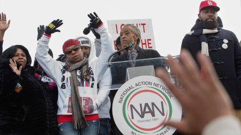 """From left, Samaira Rice, the mother of Tamir Rice; Lesley McSpadden, the mother of Michael Brown Jr.; the Rev. Al Sharpton and Michael Brown Sr., the father of Michael Brown Jr, raise their hands in the air during the """"Justice For All"""" march and rally through Washington on December 13."""