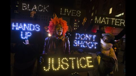 A demonstrator chants during a rally in downtown Manhattan in New York, Saturday, Dec. 13, 2014, during the Justice for All rally and march. In the past three weeks, grand juries have decided not to indict officers in the chokehold death of Eric Garner in New York and the fatal shooting of Michael Brown in Ferguson, Mo. The decisions have unleashed demonstrations and questions about police conduct and whether local prosecutors are the best choice for investigating police. (AP Photo/John Minchillo)