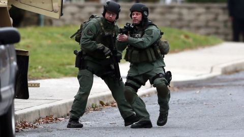 Police move near the scene of a shooting Monday, Dec. 15, 2014, in Souderton, Pa. Police are surrounding a home in Souderton, outside Philadelphia, where a suspect is believed to have barricaded himself after shootings at multiple homes. Police tell WPVI-TV the man is suspected of killing a five people Monday morning at three different homes northwest of Philadelphia.  (AP Photo/Matt Rourke)