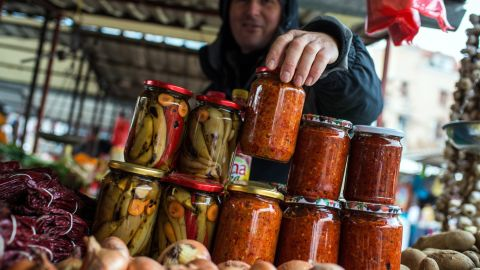 """Street markets are also a big part of life in Belgrade. Pictured here is a vendor selling jars of homemade """"Ajvar,"""" a type of relish mainly made from roasted red bell peppers."""