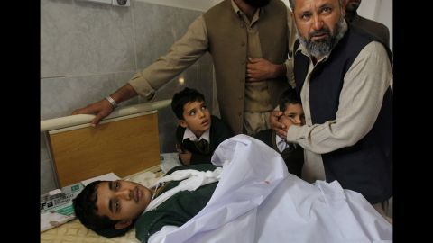 A man comforts a student standing at the bedside of an injured boy.