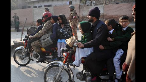 Parents leave with their children near the site of the attack.