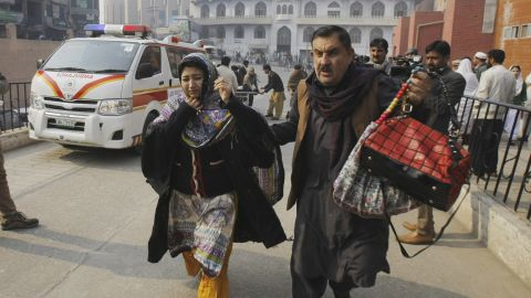 A man and woman rush to a Peshawar hospital treating victims of the attack.