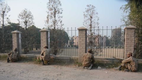 Pakistani soldiers position themselves at a fence near the besieged school.