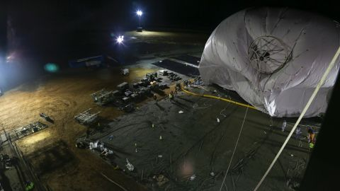 """The U.S. Army is launching two stationary """"blimps"""" at 10,000-feet over Maryland to better protect the Washington, D.C., area from cruise missiles and other possible air attacks. On December 14, personnel from the Joint Land Attack Cruise Missile Defense Elevated Netted Sensor System (JLENS) oversee the inflation of an aerostat, or stationary blimp, at Aberdeen Proving Ground, Maryland."""