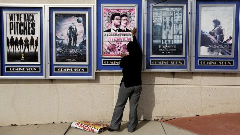 """A poster for the movie """"The Interview"""" is taken down by a worker after being pulled from a display case at a Carmike Cinemas movie theater, Wednesday, Dec. 17, 2014, in Atlanta. Georgia-based Carmike Cinemas has decided to cancel its planned showings of """"The Interview"""" in the wake of threats against theatergoers by the Sony hackers."""