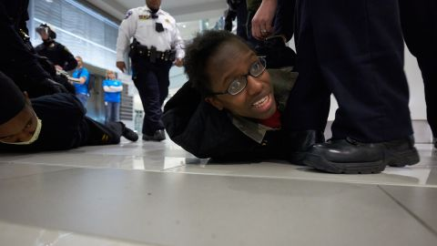 """Police arrest a """"Black Lives Matter"""" protester on Saturday, December 20, in Bloomington, Minnesota. Invoking the familiar names of blacks who died at the hands of police, including Eric Garner, Michael Brown and Tamir Rice, thousands have taken part in protests across the country calling for a more aggressive federal response to recent slayings by police."""