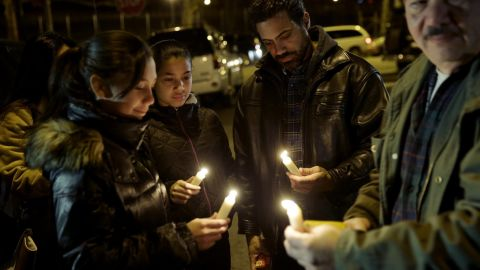 People light candles during a vigil on Sunday, December 21 for two NYPD officers who were ambushed and killed on Saturday.