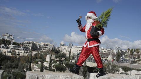 A Palestinian Santa distributes Christmas trees along the wall of Jerusalem's Old City.