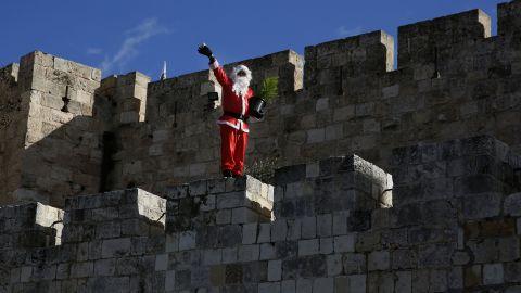 Santa waves to passers-by as he walks along Jerusalem's Old City walls.