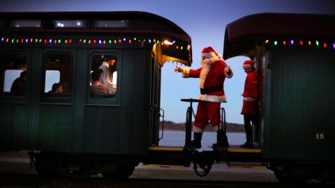 Santa greets passengers while moving between cars during the Polar Express train ride, a holiday fundraiser at the Maine Narrow Gauge Railroad Co. and Museum in Portland.