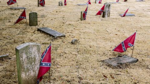 """Confederate flags mark graves at Live Oak Cemetery. Controversy erupted after the city approved a new monument at the cemetery that honors Nathan Bedford Forrest, a Confederate general accused of massacring black soldiers and a """"grand wizard"""" of the Ku Klux Klan."""