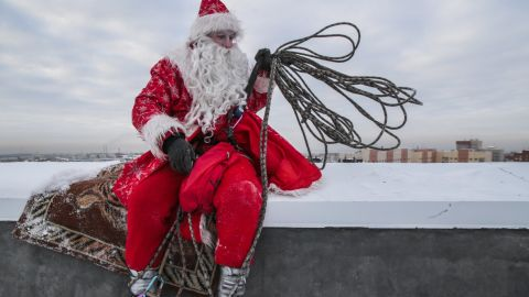 A performer dressed as Father Frost, the Russian equivalent of Santa, rests on a high-rise building in Kemerovo, Russia.