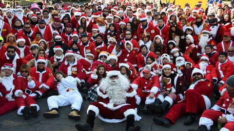"""Motorcyclists in Santa outfits take a group photo before embarking on a Christmas """"toy run"""" on their bikes in Tokyo."""