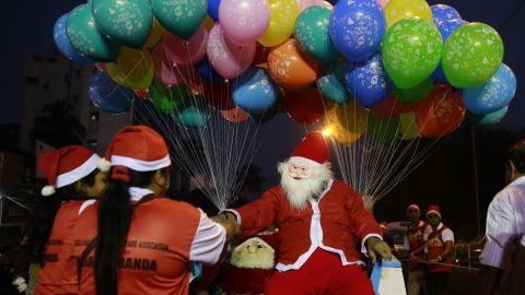 Santa distributes candy during a Christmas carnival in Mumbai, India.