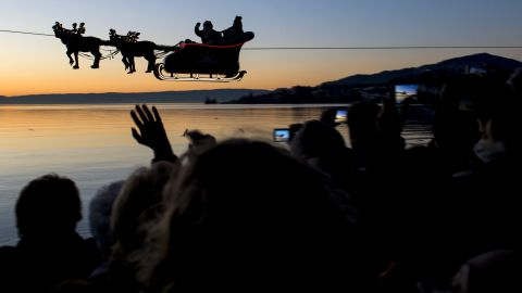 """With help from a cable, Santa and his reindeer """"fly"""" over Lake Geneva as part of the Christmas Market in Montreux, Switzerland."""