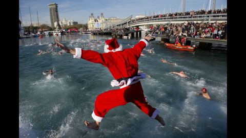 A participant wearing a Santa Clause costume jumps into the water during the105th edition of the Copa Nadal (Christmas Cup) in Barcelona's Port Vell on December 25, 2014. The traditional 200-meter Christmas swimming race gathered around 400 participants on Barcelona's old harbour.  AFP PHOTO / JOSEP LAGO        (Photo credit should read JOSEP LAGO/AFP/Getty Images)