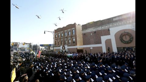 Law enforcement helicopters fly over Christ Tabernacle Church, where the casket of New York City police officer Rafael Ramos is carried by pallbearers, center, in the Glendale section of Queens, Saturday, Dec. 27, 2014, in New York. Ramos and his partner, officer Wenjian Liu, were killed Dec. 20 as they sat in their patrol car on a Brooklyn street. The shooter, Ismaaiyl Brinsley, later killed himself. (AP Photo/Julio Cortez)