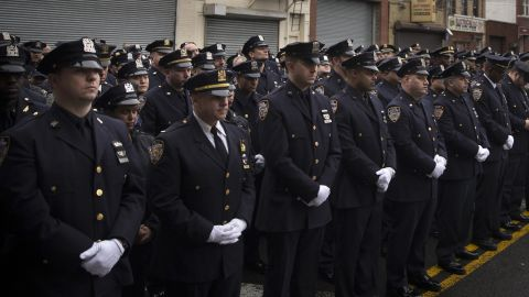 Police officers stand at attention during the funeral.
