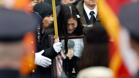 Pei Xia Chen, Liu's widow, cries while holding a picture of her husband.