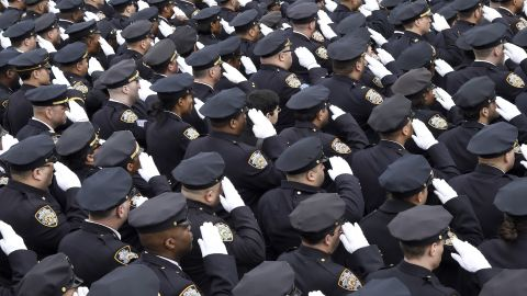 Police officers gathered for the funeral salute the fallen officer.