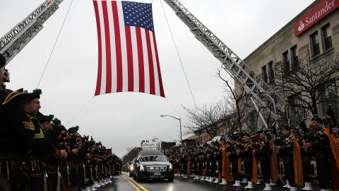 The hearse carrying Liu's body drives under a suspended American flag after the funeral.