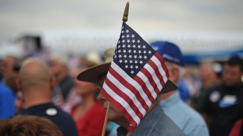 A supporter holds a US flag as Republican presidential candidate Mitt Romney  speaks at a campaign rally September 24, 2012 at Pueblo Memorial Airport in Pueblo, Colorado September 24, 2012. AFP PHOTO/Mandel NGAN        (Photo credit should read MANDEL NGAN/AFP/GettyImages)